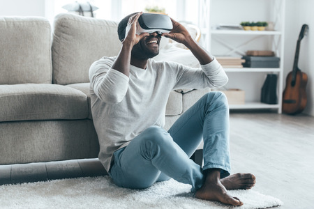 young male: Enjoying new reality!  Handsome young African man adjusting his VR headset while sitting on the carpet at home