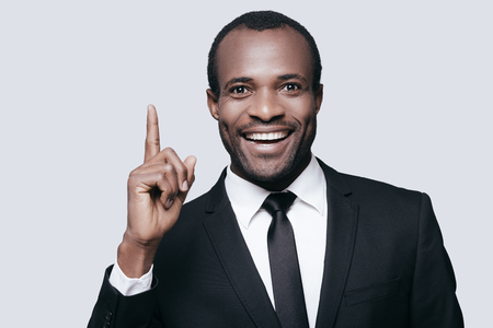 formalwear: I have an idea! Handsome young African man in formalwear pointing up and smiling while standing against grey background