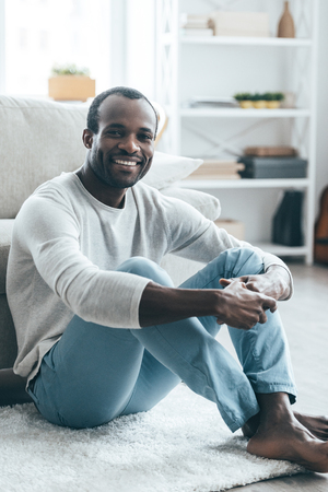 metrosexual: Enjoing weekend at home!  Handsome young African man in smart casual clothes looking at camera and smiling while sitting on the carpet at home Stock Photo