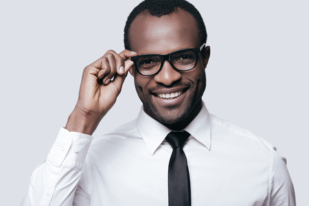 Handsome professional.  Portrait of handsome African man adjusting his eyeglasses and smiling while standing against grey background