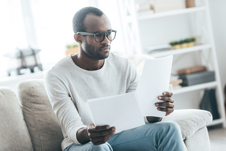 Paying attention to details. Handsome young African man working with documents while sitting on the sofa at home Stock Photo