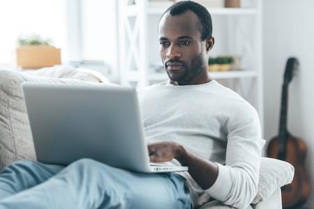 Concentrandosi su qualcosa. Bel giovane africano che esamina computer portatile con la faccia seria, mentre sdraiata sul divano di casa