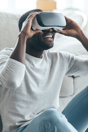 Cool!  Handsome young African man adjusting his VR headset while sitting on the carpet at home Stock Photo