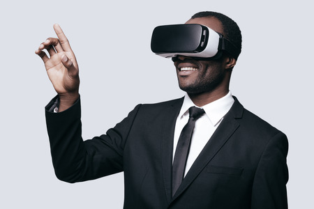 handsfree device: Enjoying new experience. Handsome young African man in VR headset gesturing and smiling while standing against grey background
