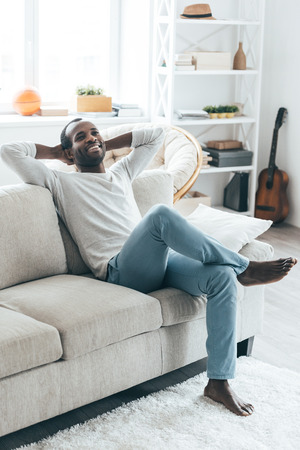 relaxing at home: Lazy day at home. Handsome young African man holding hands behind head and smiling while sitting on the sofa at home