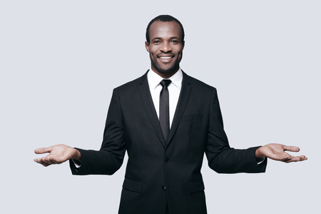 formalwear: Open to new deals. Handsome young African man in formalwear gesturing and looking at camera while standing against grey background Stock Photo