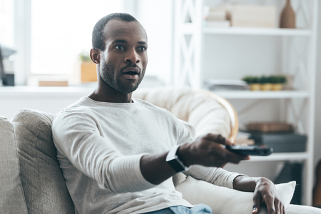 black male: Feeling surprised. Handsome young African man holding a remote control while sitting on the sofa at home