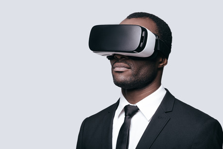 interactivity: Another reality is here! Handsome young African man in VR headset standing against grey background