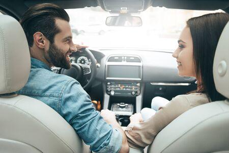 Genieten van het moment. Achteraanzicht van de jonge paar zitten op de voorste passagiersstoel en kijken naar elkaar terwijl knappe man een auto rijden Stockfoto - 67840815