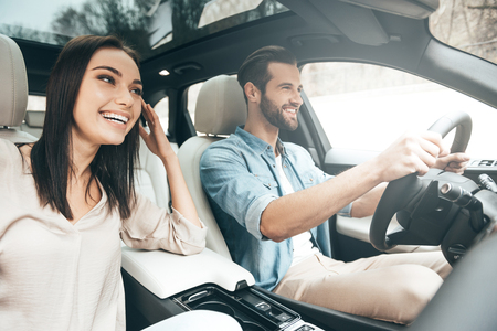 Enjoying travel. Beautiful young couple sitting on the front passenger seats and smiling while handsome man driving a car