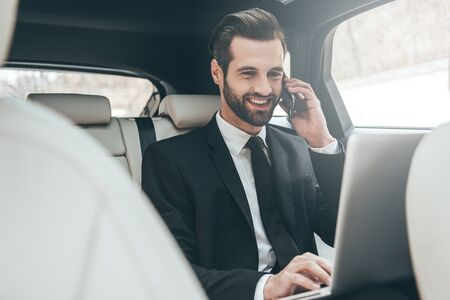 back seat: Focusing on work. Handsome young businessman working on his laptop and talking on the phone while sitting on the back seat of the car