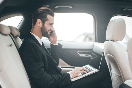 man with laptop: Time to make decision. Confident young businessman working on his laptop and talking on the phone while sitting in the car Stock Photo