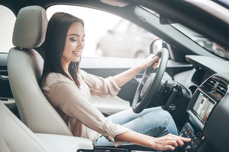 お気に入りの音楽を探しています。若い魅力的な女性は笑みを浮かべて、車を運転中にボタンを押す