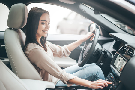 Searching for favorite music. Young attractive woman smiling and pushing buttons while driving a car