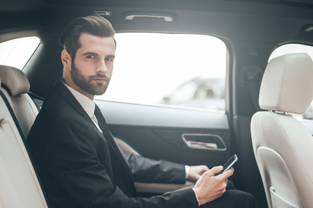 Thinking about new possibilities. Confident young businessman setting his smart phone and looking at camera while sitting in the car photo