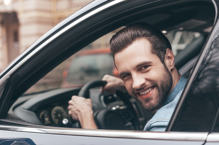 Nice travel. Confident young man smiling and looking at camera while driving a car photo
