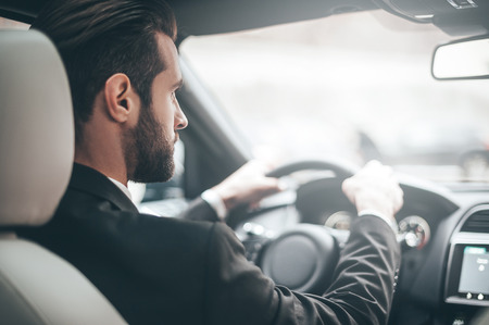 Concentrating on the road. Rear view of young handsome man looking straight while driving a car photo