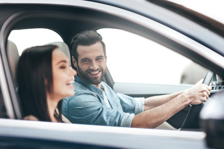 driving a car: Enjoying the trip.  Young couple sitting in the car and smiling while handsome man holding hands on the steering wheel