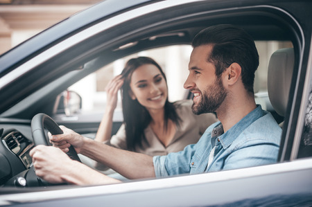 Careful driving. Beautiful young couple sitting on the front passenger seats and smiling while handsome man driving a car photo