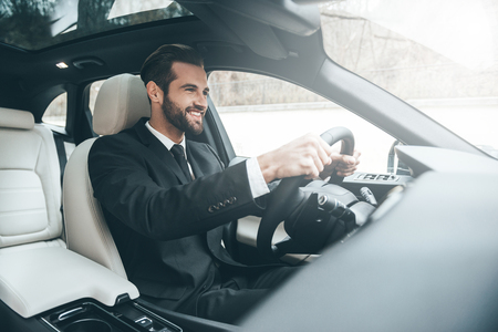 On the way to success. Confident young businessman sitting on the front seat and smiling while driving a car photo