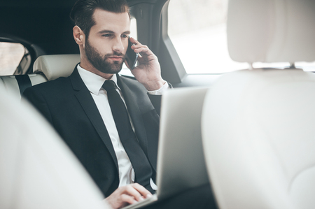 Always available. Handsome young businessman working on his laptop and talking on the phone while sitting in the car photo
