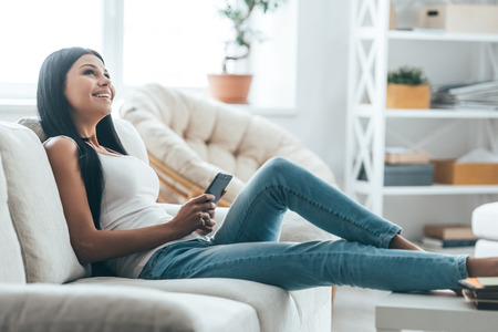 Texting to boyfriend. Attractive young woman holding mobile phone and looking away while relaxing on the couch at home