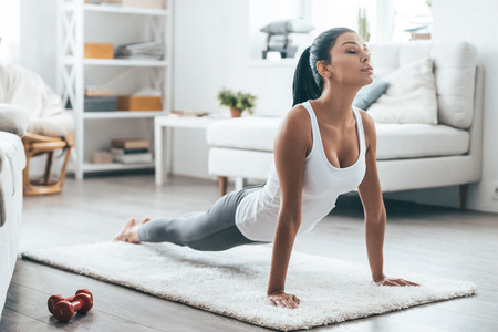adult woman: Time for yoga.  Attractive and healthy young woman doing exercises while resting at home