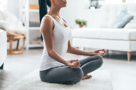 Time for yoga. Close up of attractive young woman exercising and sitting in yoga lotus position while resting at home