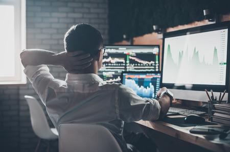 Přemýšlejte o nových řešeních. Zadní pohled na mladého muže v příležitostné oblečení drží ruku na zadní straně hlavy a pracuje, zatímco sedí u stolu v kreativní kanceláři Reklamní fotografie