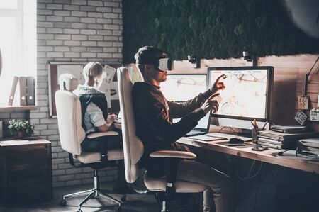 Enjoying new reality. Handsome young man wearing virtual reality headset and gesturing while sitting at his desk in creative office near young woman