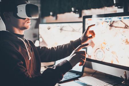 handsfree device: Experiencing virtual reality. Handsome young man wearing virtual reality headset and gesturing while sitting at his desk in creative office