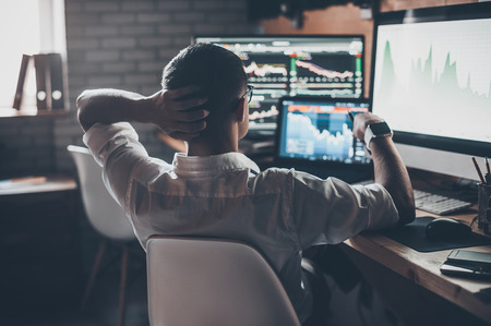 Developing new approaches. Rear view of young man in casual wear holding hand on the back of the head and working while sitting at the desk in creative office Stockfoto