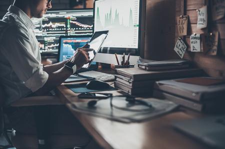 Met behulp van moderne technologieën op het werk. Close-up van jonge zakenman werken op digitale tablet tijdens de vergadering op het bureau in creatieve kantoor Stockfoto