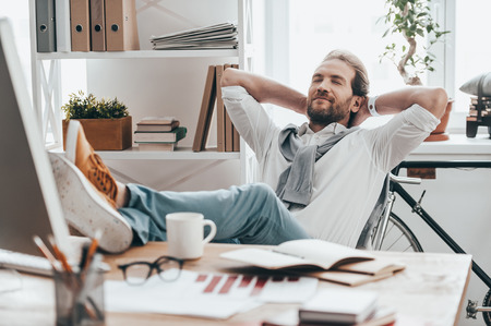 Enjoying little break. Handsome young man with closed eyes holding hands behind head and resting with feet on desk while sitting on working place in creative office Stock Photo