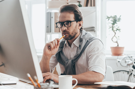 Full concentration. Handsome young man touching his chin with pencil and working while sitting on working place in creative office Stock Photo