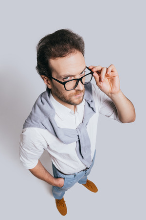 Looking for you! Top view of handsome young man in smart casual clothes adjusting his eyeglasses and looking at camera while standing against grey background Reklamní fotografie