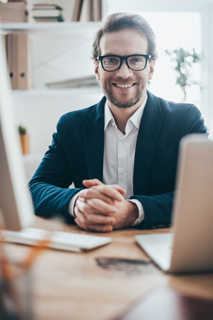 only man: Ready to hear you out. Handsome young man in eyeglasses smiling and looking at camera while sitting on working place in creative office Stock Photo