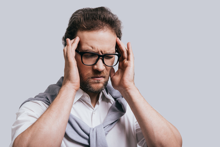 closed society: Terrible headache! Handsome young man in smart casual clothes touching his head with hands and keeping eyes closed while standing against grey background
