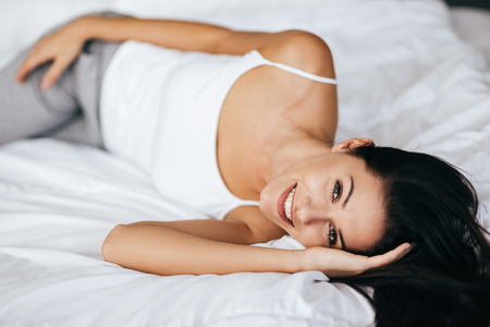 Dreaming of something. Attractive young woman looking at camera and smiling while lying on the bed at home