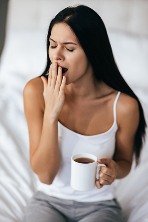 Impossible to wake up! Young beautiful woman with long dark hair holding a cup and yawning while sitting on the bed at home