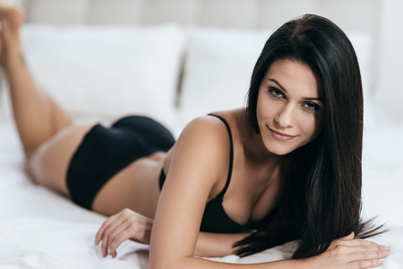 5851e754f0c0 Irresistible mujer joven en ropa interior negro mirando a cámara mientras  está acostado en la cama en casa