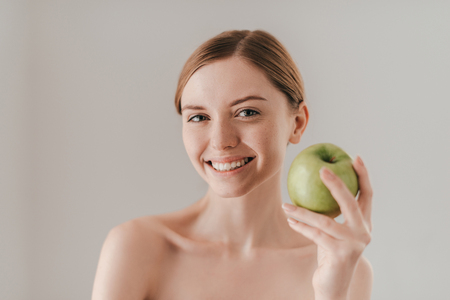 healthy looking: Healthy lifestyle. Attractive young woman holding apple and looking at camera while standing against background