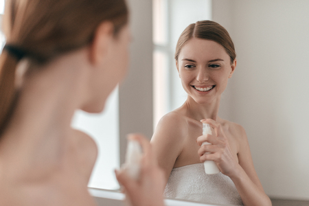 water spray: Body care procedures. Over the shoulder view of young beautiful woman applying water spray while standing in front of the mirror