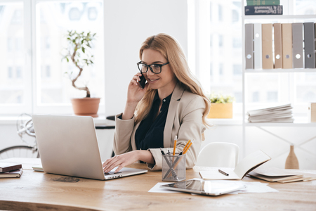 the place is important: Important business talk. Confident young woman in smart casual wear talking on the mobile phone and smiling while sitting at her working place in creative office Stock Photo