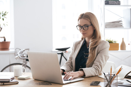 New solution every day. Confident young woman in smart casual wear working on laptop while sitting at her working place in creative office Foto de archivo