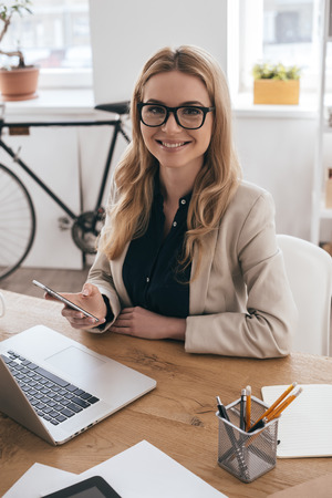 casual office: Beautiful business lady. Gorgeous young woman in smart casual wear holding smart phone and looking at camera while sitting at her working place in creative office Stock Photo