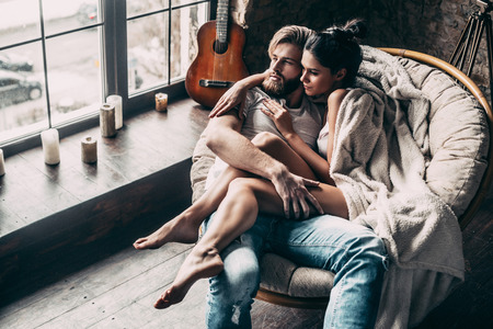 Romantic couple. Top view of beautiful young loving couple embracing and looking through window while sitting in big cozy chair at home
