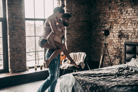 They belong together. Young couple enjoying free time at home while shirtless man carrying attractive woman on shoulders Stock Photo