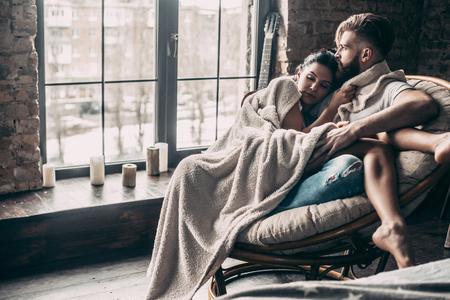 Altijd haar beschermen. Mooi jong paar omvat met deken die samen terwijl thuis het zitten in een leunstoel rusten Stockfoto
