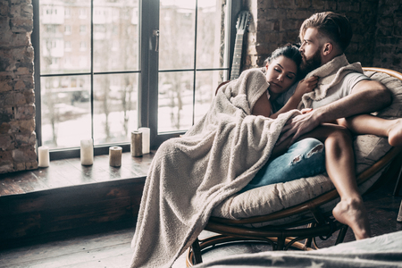 Always protecting her. Beautiful young couple covered with blanket resting together while sitting in an armchair at home Фото со стока